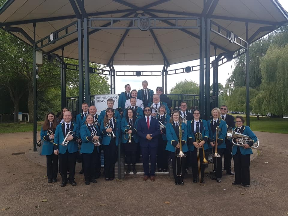 Members of City of Birmingham Brass Band stand in front of bandstand holding their instruments
